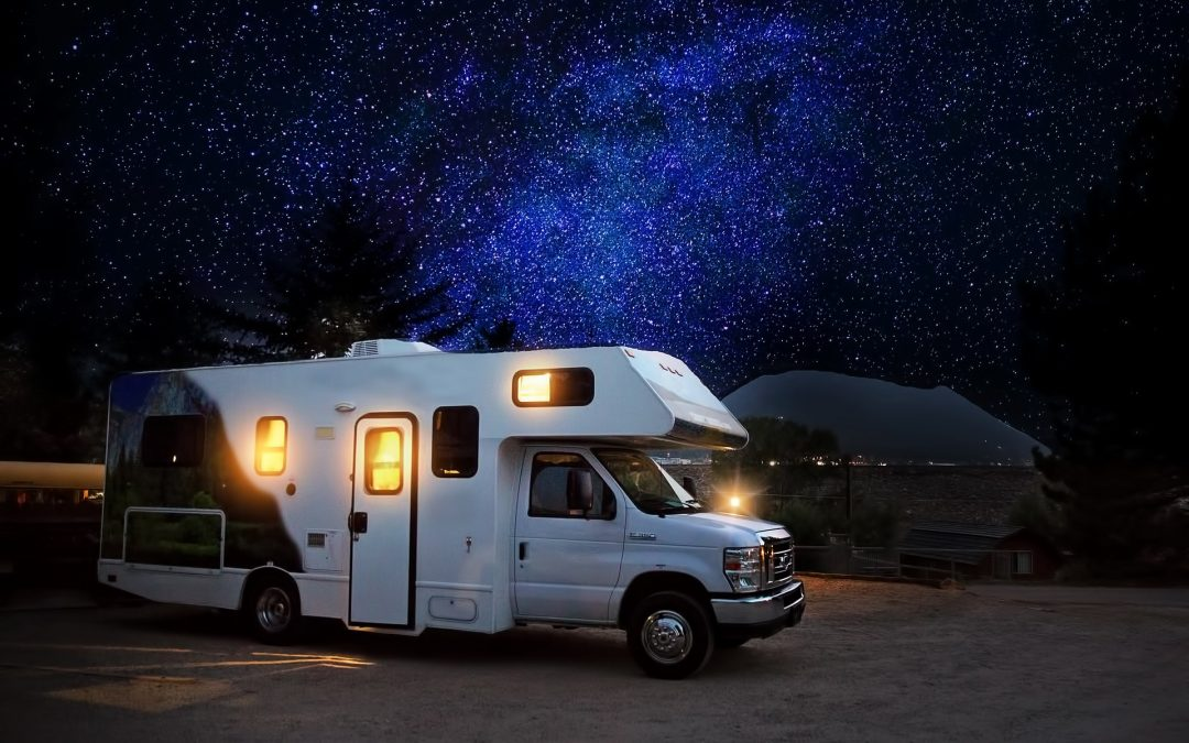 RV against a star studded sky traveling, likely with a collapsible ladder