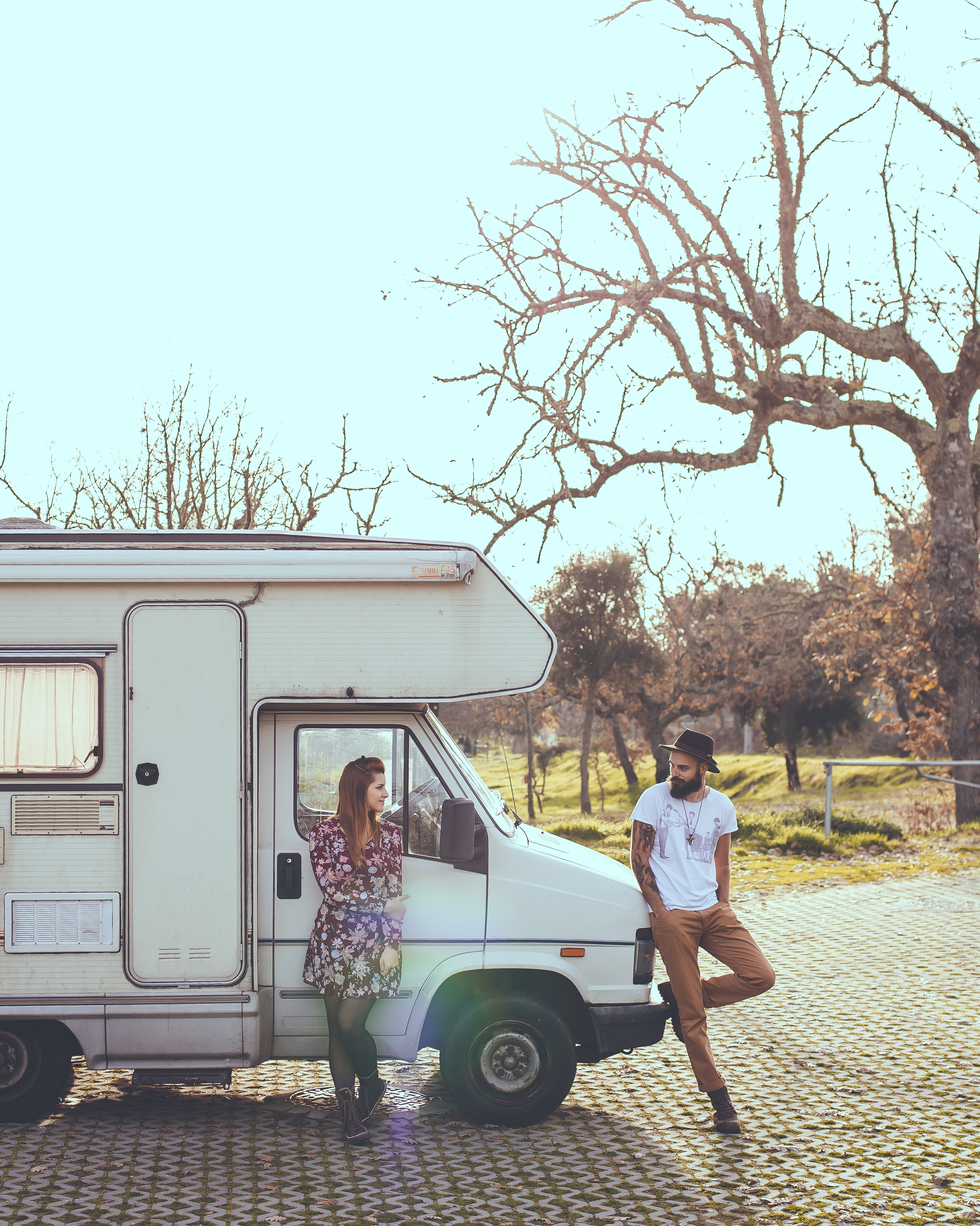 man and woman leaning next to an rv